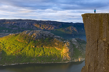 Person standing on The Preikestolen (Pulpit rock) at the Lysefjorden. Forsand, Rogaland, Norway, June 2012.