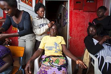 Kenyan women having hair braided, Kisumu region, Kenya, December 2013.