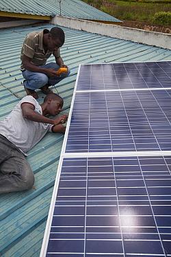 Solar energy technicians checking panel installation, Rwanda, April 2014.