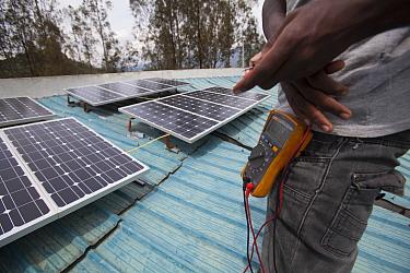 Solar energy technician with a multimeter, Rwanda, April 2014.
