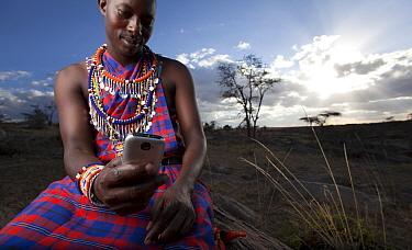 Maasai man using mobile phone, Mara region, Kenya, September 2013.