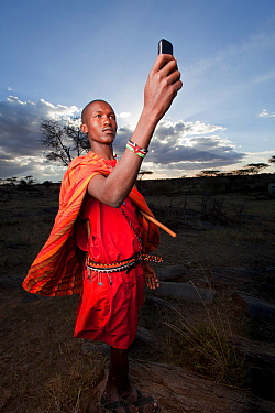 Maasai holding up mobile phone to get better reception, Mara Region, Kenya, September 2013.
