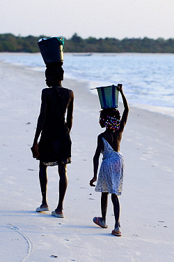 Two girls on their way along beach to collect water, Orango Island, Bijagos UNESCO Biosphere Reserve, Guinea Bissau, February 2015.