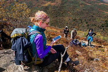 Woman using a mobile phone miles away from any city along the Jhomolhari Trek.  Bhutan, October 2014. Model released.
