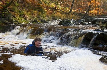 Photographer Theo Bosboom taking photographs in water of La Hoegne mountain stream, Belgium
