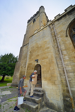 Nest box for Common swifts (Apus apus) carried by Roger Becket and Peter Grayshon into Holy Trinity church to be fitted in the bell tower, Bradford-on-Avon, Wiltshire, UK, June.