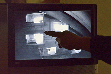 Householder points to a monitor linked to an infra red camera in her attic focused on a group of perspex backed swift nestboxes, Cambridge, UK, July. Model released.