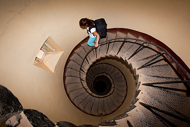 Woman walking on the long staircase inside the Lighthouse, Sanganeb reef, Sudan, Red Sea