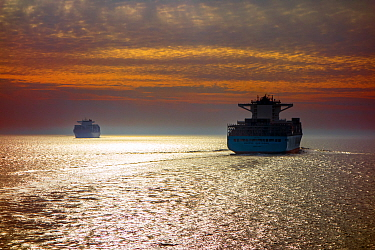 Two container ships / cargo vessels sailing at sunset, North Sea