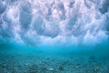 Wave breaking over the rubble zone close to the reef crest of a coral reef. Baa Atoll, Maldives. Indian Ocean.