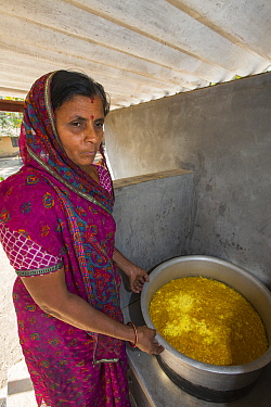 Woman with solar cooker used to cook food for the school students at Muni Seva Ashram, Goraj, near Vadodara, India. December.