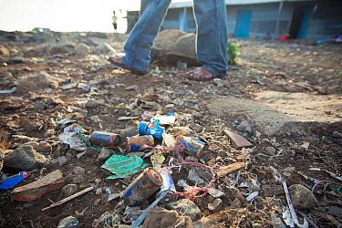 Man walks past discarded batteries littering the ground on Remba Island, Lake Victoria, Kenya