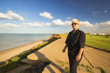 Woman standing next to the edge of collapsing coastal cliffs. She is at the location where her house used to be fore she was evacuated. Aldbrough, Yorkshire, England, East Coast, UK August 2013.