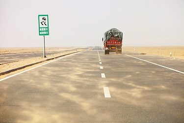 Dust storm blowing sand across highway in Inner Mongolia during severe drought, China, March 2009.
