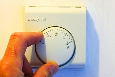 Setting the central heating thermostat at a cooler temperature to save energy.