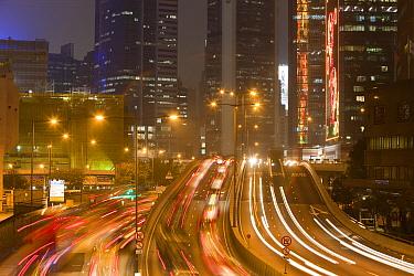 Office blocks lit up at night and cars in Hong Kong, China. February 2010.