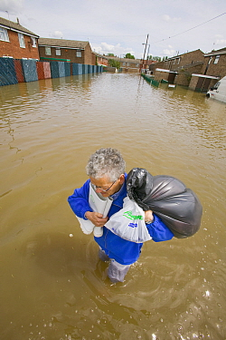 Resident carrying belongings through flood waters,  Toll Bar near Doncaster, South Yorkshire, England, UK, 28th July 2007.