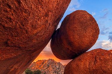 Storm clouds at sunset over balancing  eroded boulder, Texas Canyon, Little Dragoon Mountains, Chihuahuan Desert, Arizona, USA. September.