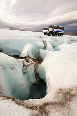 Twenty ton ice explorer truck  next to a Moulin, or sink hole for meltwater. Iceland, September 2010.