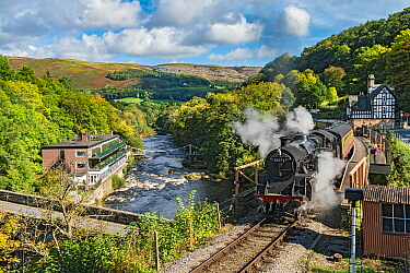 Steam train leaving Berwyn station beside the River Dee and the Chainbridge Hotel on the Llangollen Heritage Railway  to Corwen North Wales, UK, September 2017.