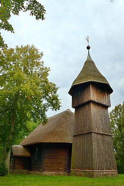 Old wooden church and belfry with thatched roofs from Masuria, now within the Ethnographic Park, Olsztynek, Poland, September 2017.