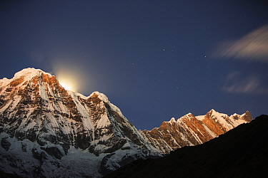 Night sky over Annapurna South and Annapurna Fang, with a glow from the moon setting behind the peak. Annapurna Sanctuary, Himalayas, Nepal, December 2012.