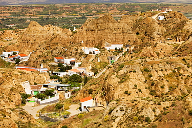 Old Cave houses in Guadix, Andalucia, Spain. Up to 10,000 people still live in cool underground houses dug out of the rock, this area known as the Barrio Santiago is a mix of modern cave houses and an...