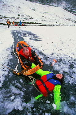 Members of the Langdale Ambleside Mountain Rescue Team rescue a man fallen through ice on Rydal Water, Lake District, England, UK.