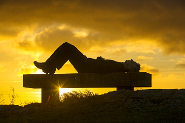 A walker relaxing at sunset,  on Orrest Head above Windermere, Lake District UK. December 2012