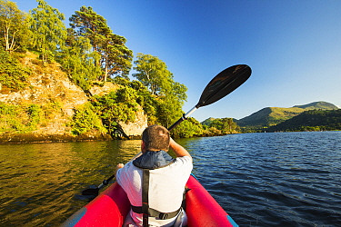 Middle aged man paddling in an inflateable kayak on Ullswater, Lake District, UK. July 2014