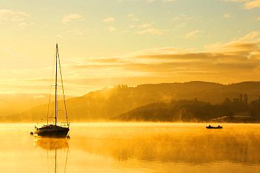 Sunrise over men fishing in a boat on Lake Windermere in Ambleside, Lake District, UK. December 2014