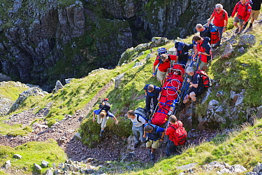 Members of Langdale Ambleside Mountain Rescue Team carrying an injured walker from the fells in Langdale, Cumbria, England, UK. August 2007