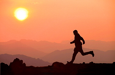 Silhouette of man running at sunset, Windermere, Lake district, England, UK. April 2011