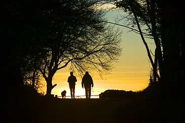 Walkers silhouhetted  on a country lane near Troutbeck, Lake District, England, UK. November 2005