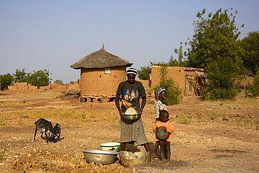 Woman winnowing grain with family, Burkina Faso,  December