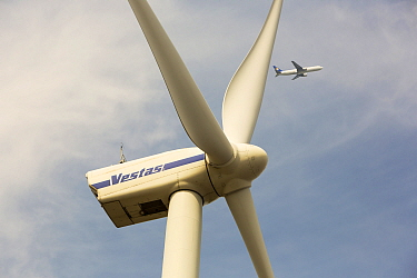 Wind turbine in Amsterdam with a plane flying past having taken off from Schiphol airport, Netherlands. May 2013