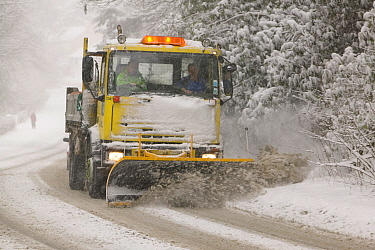A snow plough driving in heavy snow, clearing the road  in Ambleside, England, UK. March 2006
