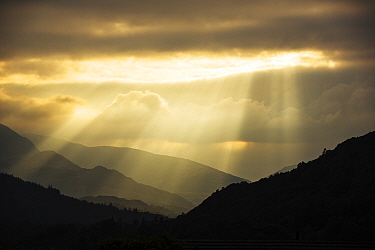 Shafts of light at dusk over Wrynose pass and the Coniston hills from Ambleside, Lake District, England, UK. September 2015