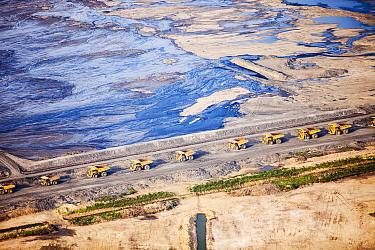 Massive dump trucks with  load with tar sand in a mine north of Fort McMurray, Alberta, Canada. August 2012