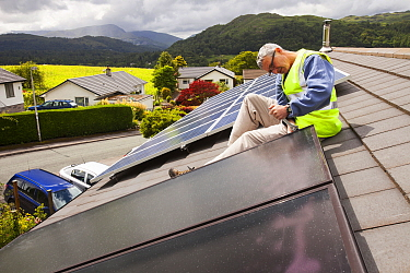 Workman fitting solar thermal panels for heating water, to a house roof, Ambleside, Cumbria, UK,. June 2012