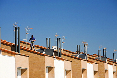 Man working on solar water heaters on a house roof in Sanlucar La Mayor in Andalucia, Spain. May 2011