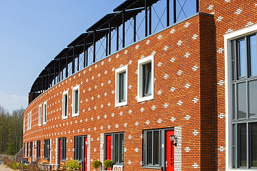 Houses in Almere with solar PV panels on the roof. It is the Netherlands youngest town, in Flevoland, which was reclaimed from the sea. This planned city is very green, with space heating provided fro...