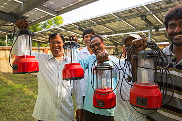 Man with new solar lanterns from  WWF project to supply electricity to a remote island in the Sunderbans, Ganges Delta, India. December 2013