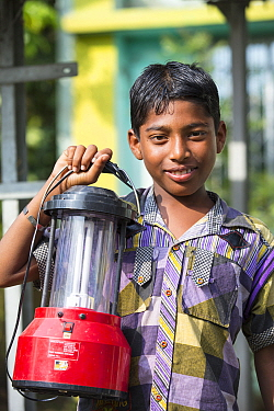 Boy holding a solar lantern, charged from the solar panelsfrom WWF project to supply renewable electricity to a remote island in the Sunderbans, Ganges, India. December 2013
