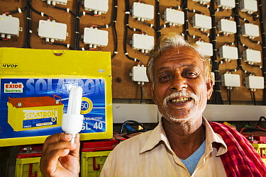 Old man with a low energy light bulb which he can use to power house with solar charged batteries from WWF project to supply electricity to a remote island in the Sunderbans, Ganges Delta, India. Dece...