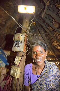 Dalit woman / untouchable woman in her hut, illuminated by an electric light, powered by an A4 sized solar panel, that charges a battery, and enables her to have light. Karnataka, India. December 2013