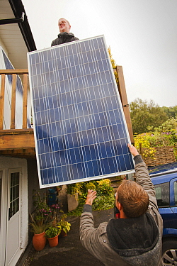 A technician fitting solar photo voltaic panels to a house roof in Ambleside, Cumbria, UK. August 2011