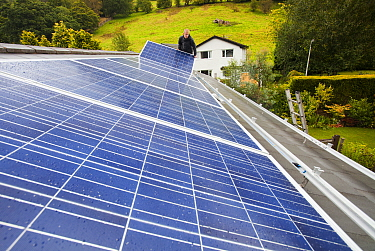 Technicians fitting solar photo voltaic panels to a house roof in Ambleside, Cumbria, UK. August 2011
