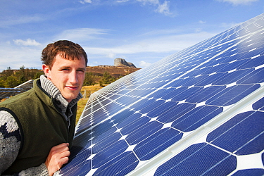 An Eigg crofter and Eigg Electric employee next to their aray of solar PV panels. Isle of Eigg, Scotland, UK. May 2012