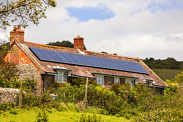 Solar panels on an old house on the Dorset coast near Charmouth, UK. June 2012